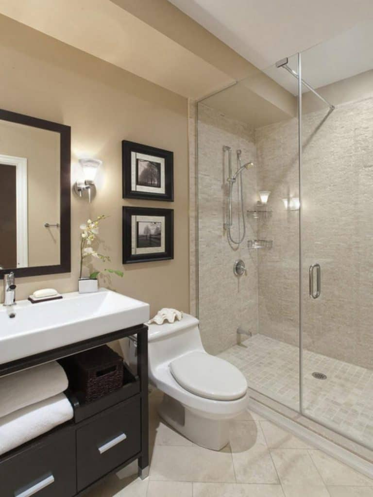 Phòng tắm nhỏ có thiết kế đơn giản, có buồng tắm kính và tủ gỗ dưới bồn rửa.